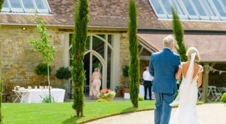 bride walking down the aisle to countryside barn wedding venue in Dorset the tithe barn