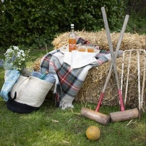 country fair promotion image of croquet, straw bells, symondsbury apple juice, home and garden products of handbag, flowers, scarf, blankets